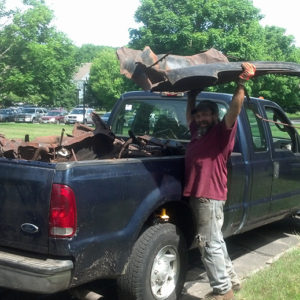 Frank Shows Off A Section Of The Roof, Which They Used As A Sled To Transfer The Heaviest Parts From The Wreck Site To A Steep Embankment. At That Point, They Winched It Up The Hill To The Pick-up Truck.